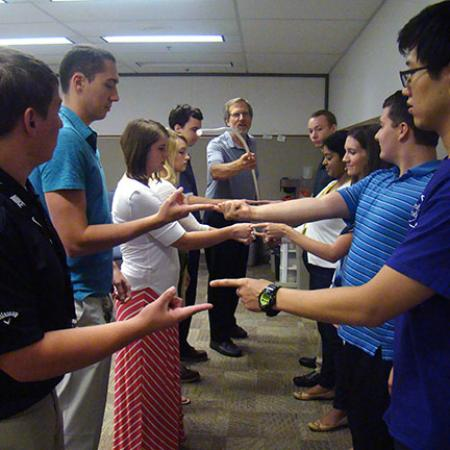 2016 Interns participate in a group icebreaker during a weekly meeting.